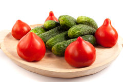 Tomatoes and gherkins. On a wooden board isolated on white background Stock Images