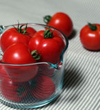 Tomatoes in a glass measuring cup with some scattered in the background. All are very ripe and deep red Stock Photos