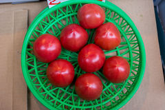 Tomatoes in a green basket. Some tomatoes in a green basket over a wooden surface. full top view of pile of cherry tomatoes. image in sunny day Stock Photo