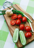 Tomatoes and green onions on cutting board Royalty Free Stock Image