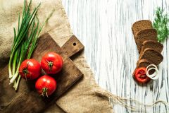 Tomatoes, green onions, dill, quail eggs, bread, on a white boar Royalty Free Stock Photo