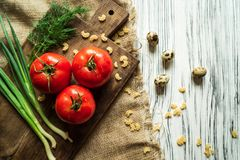 Tomatoes, green onions, dill, quail eggs on a white board Royalty Free Stock Images