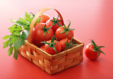 Tomatoes and green parsley in basket Stock Photo