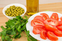 Tomatoes, green peas, parsley and olive oil on board. Tomatoes, green peas, parsley and olive oil in bottle on board Royalty Free Stock Photos