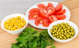 Tomatoes, green peas, sweet corn and parsley on board Royalty Free Stock Image