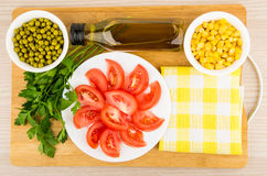 Tomatoes, green peas, sweet corn, parsley and olive oil Royalty Free Stock Image