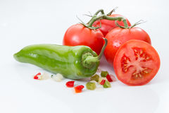 Tomatoes with a green pepper and diced peppers and onions. Stock Image
