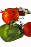 Tomatoes and green pepper dropped into water Stock Images