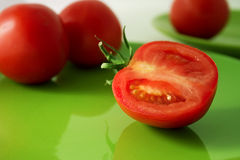 Tomatoes on a green plate Stock Image