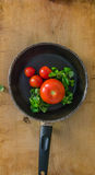 Tomatoes and green salad in a pan Stock Photos