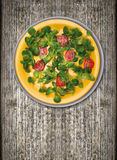 Tomatoes with green salad, in yellow  plate Royalty Free Stock Photography