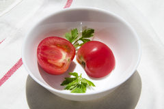 Tomatoes. And greens in the plate on the tablecloth Stock Photography