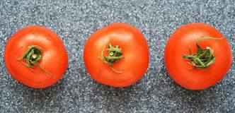 Tomatoes on grey background. Juicy red tomatoes on grey background. proper nutrition, natural product royalty free stock photography