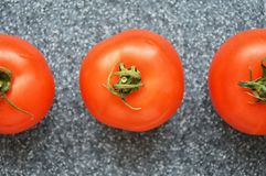 Tomatoes on grey background. Juicy red tomatoes on grey background. proper nutrition, natural product stock photography