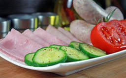 Tomatoes, ham, cucumber and white sausage on a plate Stock Image