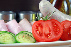 Tomatoes, ham, cucumber and white sausage on a plate Stock Photos