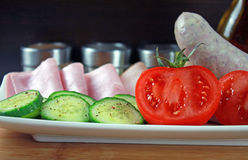 Tomatoes, ham, cucumber and white sausage on a plate Royalty Free Stock Photography
