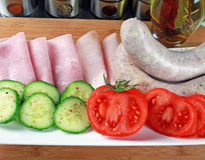 Tomatoes, ham, cucumber and white sausage on a plate Stock Photography