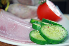 Tomatoes, ham, cucumber and white sausage on a plate Royalty Free Stock Photo