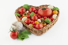 Tomatoes in heartshaped basket. Tomatoes in different sizes in heartshaped basket. White background. Garlic and basil royalty free stock photo