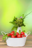 Tomatoes and herbs. Tomatoes in a basket and decorative bouquet of herbs in a vase Royalty Free Stock Photo