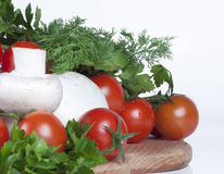 Tomatoes, herbs and mushrooms. On a kitchen board Royalty Free Stock Photo
