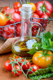 Tomatoes with herbs  and oil Stock Photography