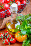 Tomatoes with herbs  and oil. On wooden table Royalty Free Stock Photo