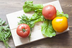 Tomatoes and herbs. Pink and yellow tomatoes with herbs on a wooden board stock photos