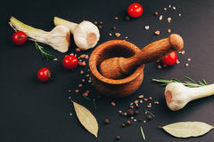Tomatoes, herbs, spices and mortar on black Stock Photos