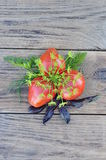 Tomatoes and herbs. Three tomatoes and greens lying on a wooden board royalty free stock photography