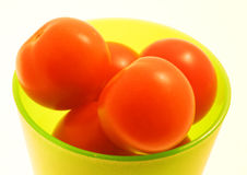 Tomatoes-II. Green plastic cup holding red tomatoes, over a white background royalty free stock photo