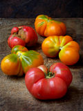 Tomatoes irregular shape of different varieties and colors on wooden background. Stock Photos