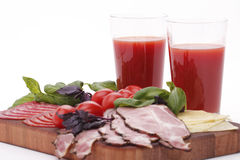 Tomatoes, juice, cheese and ham. On the board Royalty Free Stock Image