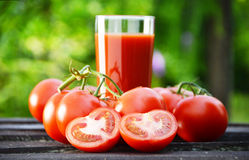 Tomatoes and juice in the garden. Organic food Royalty Free Stock Photography