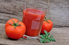 Tomatoes juice in a glass on table Stock Image