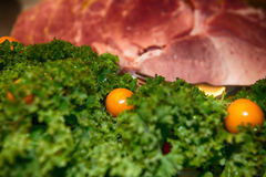 Tomatoes, kale and ham. Tomatoes and kale in front of Christmas Ham stock photo