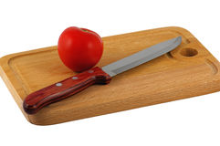 Tomatoes On Kitchen. The tomato and knife lay on a chopping board. Closeup. Isolated on a white background Royalty Free Stock Photography