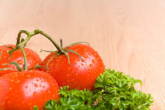 Tomatoes on kitchen countertop. Tomatoes and parsley with water droplets on wooden kitchen counter top Stock Photo