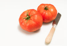 Tomatoes and knife Stock Images