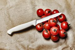 Tomatoes With Knife on Brown Surface Royalty Free Stock Images