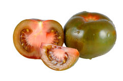 Tomatoes kumato. Whole tomatoes and chopped of the variety kumato trimmed and isolated Royalty Free Stock Photography