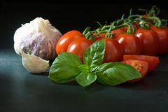 Tomatoes with a leaf of basil, garlic, clove of garlic and slice Stock Photo