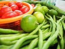 Tomatoes, lemons and cow-peas on banana leaf Royalty Free Stock Image