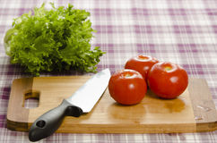 Tomatoes and lettuce on table with chopping board and knife. Stock Photos