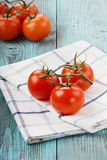 Tomatoes on a linen napkin. On a turquoise colored wooden surface Royalty Free Stock Photography