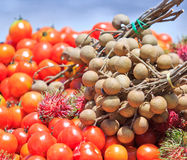Tomatoes, longans and rambutans. Fresh mixed fruits from the farmland Royalty Free Stock Images