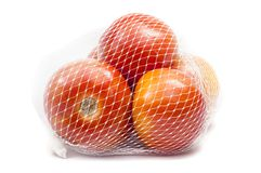 Tomatoes in mesh bag. And  on white Stock Photo