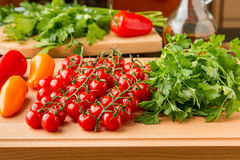 Tomatoes, mini bell peppers and parsley on wooden cutting board. Stock Photos