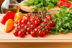 Tomatoes, mini bell peppers and parsley on wooden cutting board. Royalty Free Stock Photos